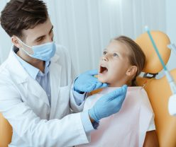 Dental care, routine check ups and pediatric dentistry. Millennial serious man in white coat, protective mask and gloves examines mouth of little kid in medical chair in modern clinic interior